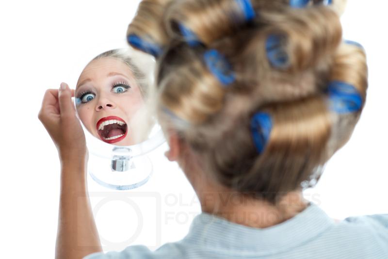 Hausfrau mit Spiegel und Lockenwickler