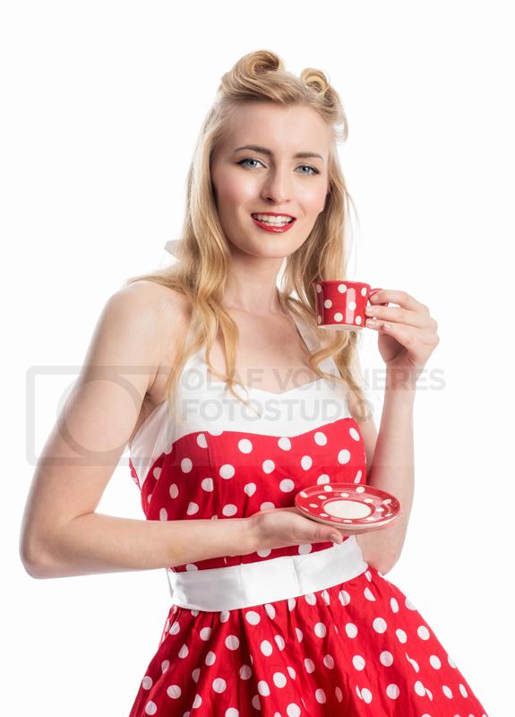 Frau im Pünktchenkleid mit Kaffee