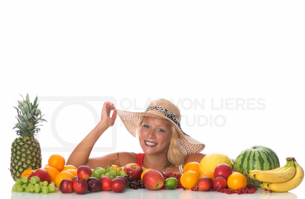 Frau mit Sommerhut und Früchten