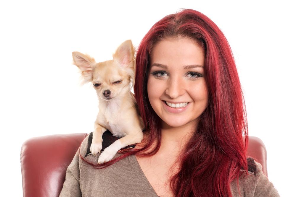 rothaarige Frau mit kleinem Hund Stockfoto