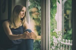 verträumtes Mädchen am Fenster Stockfoto