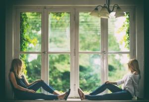 2 Freundinnen am Fenster Stockfoto